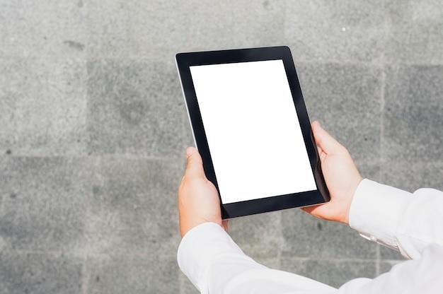 コンクリートの壁を背景にビジネスマンの手に白い画面でクローズアップタブレットモックアップ。