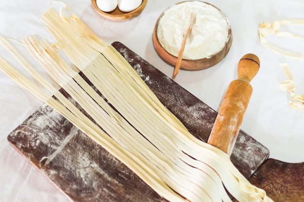 Close-up of tagliatelle pasta on wooden board with flour and rolling pins