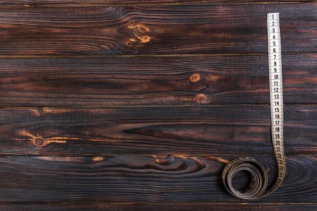 Закройте вверх по измеряя ленте портноя на предпосылке деревянного стола. белая измерительная лента мелкой глубины поля