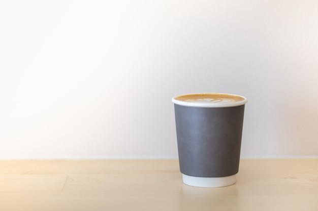 Close up of take away paper cup of hot coffee latte with copy space.