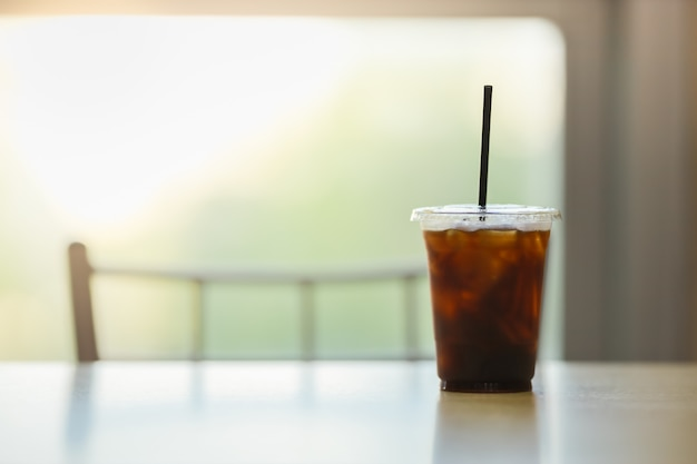 Close up of take away plastic cup of iced black coffee (americano) in restaurant on table with copy sapce.