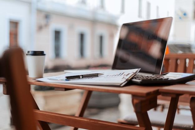 Закройте вверх. кофе на вынос и финансовый график на террасе кафе. фото с копировальным пространством.