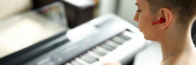 Close-up of talented female playing on synthesizer. modern instrument for musician. short haired young woman performing melody on piano. music and hobby concept