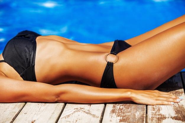 Загорелое стройное женское тело крупным планом возле бассейна