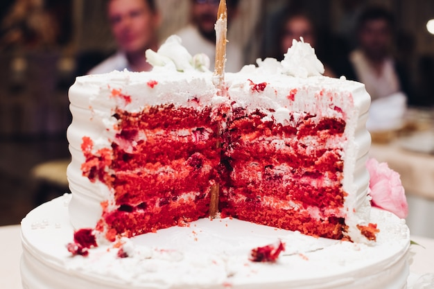 Close-up tasty big appetizing fresh piece of layered biscuit cake covered by white whipped cream icing. beautiful dessert food serving for banquet event people guest at background. red velvet