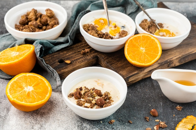 Close-up tasty breakfast bowls with granola and orange