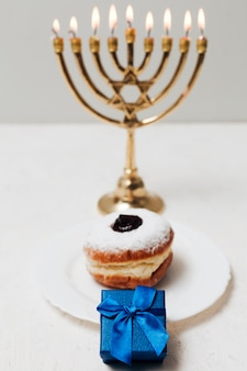 Close-up tasty donut and a menorah