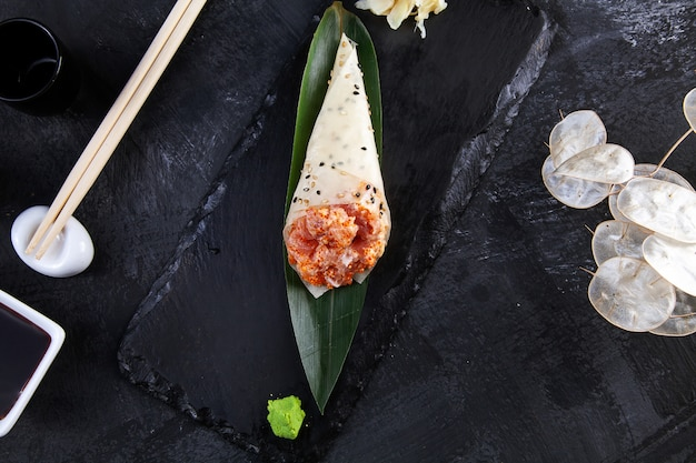 Close-up of tasty hand roll sushi in mamenori with tuna and tobico caviar served on dark stone plate with soy sauce and ginger.