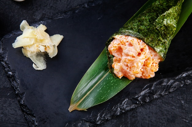 Close-up of tasty hand roll sushi with salmon and tobico caviar served on dark stone plate with soy sauce and ginger.
