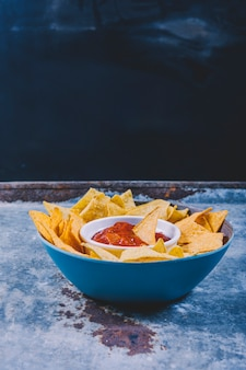 Close-up of tasty nachos and bowl with salsa sauce on metal table