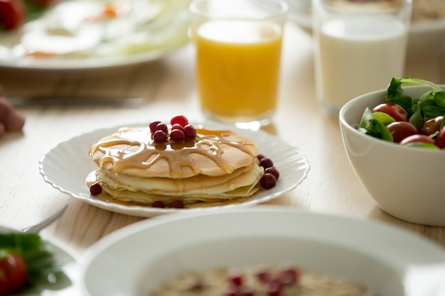 Close up of tasty pancakes served with syrup and berries