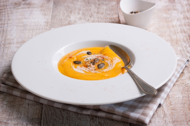 Close-up of tasty pumpkin soup with spoon