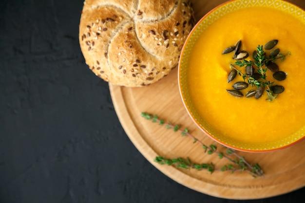 黒の背景に、種、ハーブ、パンを添えた、おいしいビーガン自家製カボチャスープのクローズアップ。