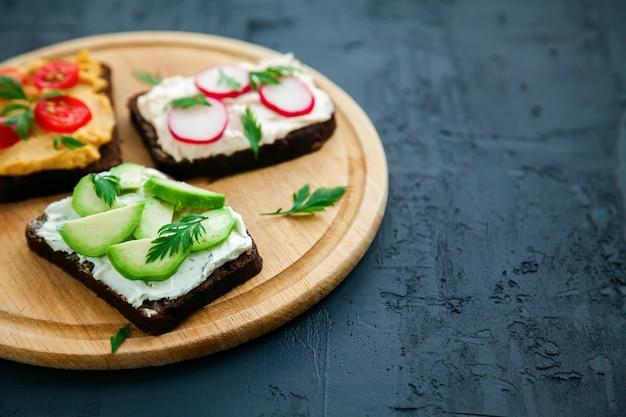 Вкусные вегетарианские тосты из ржаного хлеба крупным планом с творогом, хумусом, авокадо, редисом и помидорами. деревянная доска на черном фоне, копия пространства