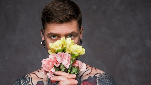Close-up of tattoo young man with pierced ears holding pink and yellow carnation flowers in front of his mouth