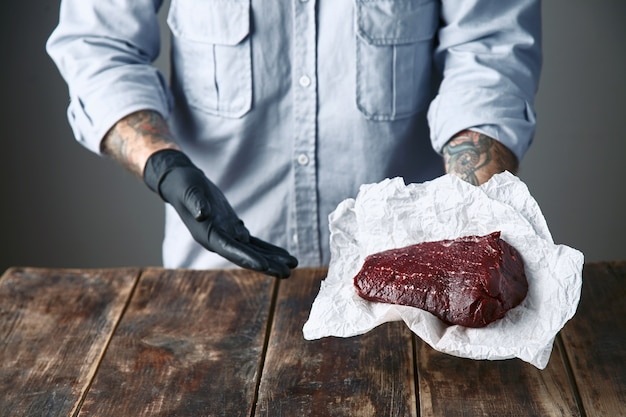 Close up, tattooed hands in black gloves offers steak meat