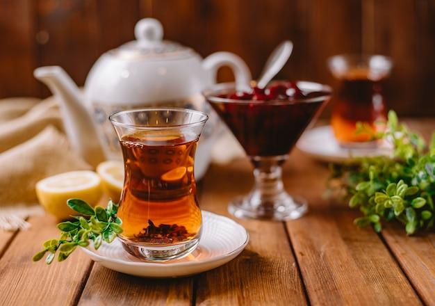 Close up of tea in armudu glass served with azerbaijani murabba and lemon