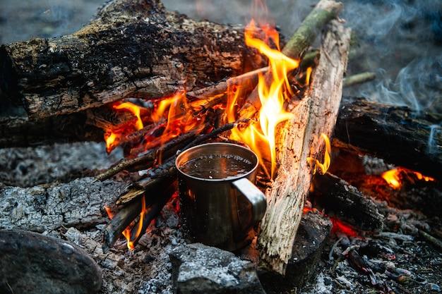Close up of tea in metal mug heats up on bonfire