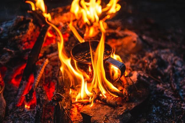 Close up of tea in metal mug heats up in bonfire