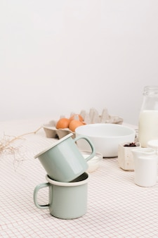 Close-up of tea mugs in front of organic ingredients over table