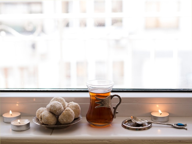 Close up tea and nastar sitting on window sill
