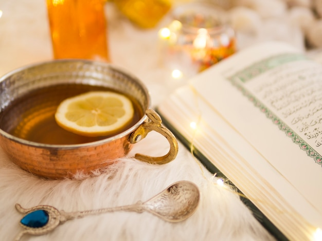 Close up tea next to opened  quran