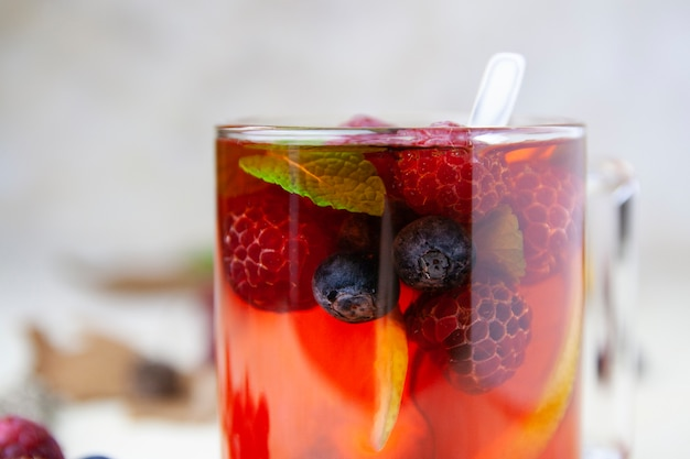 Close-up of tea with berry and lemon