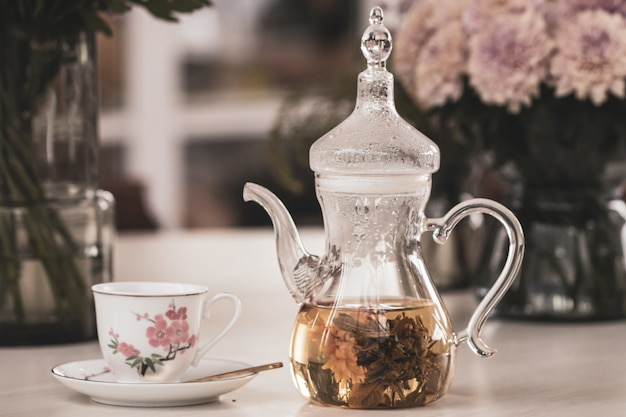 Close up teapot and cup with blooming tea flower and pink chrysanthemum flowers in glass vase on table.