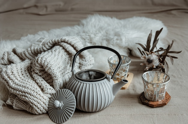 Close-up of teapot in scandinavian style with tea with knitted element and decor details.