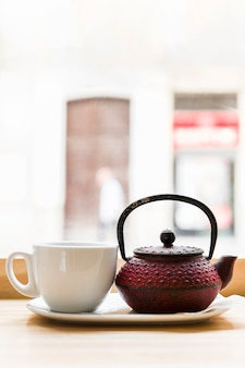 Close-up of teapot and white tea cup on wooden surface