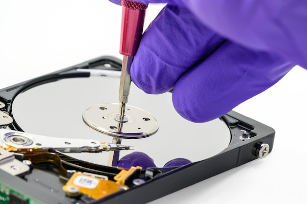 Close up of technician repairing hard disk drive by screwdriver in the lab. concept of data, hardware, technician and technology.