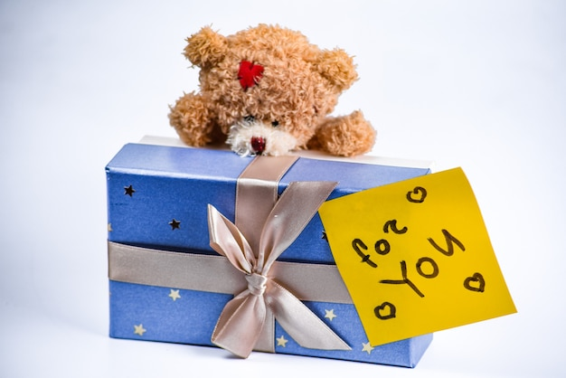 Close up of a teddy bear with a gift box
