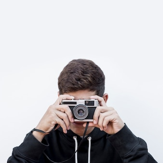 Close-up of a teenage boy taking photography click on retro vintage photo camera against white background