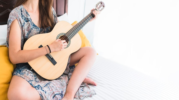 Close-up of a teenage girl sitting on bed playing guitar