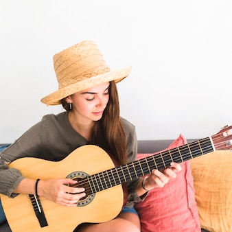 Close-up of a teenage girl wearing hat playing guitar
