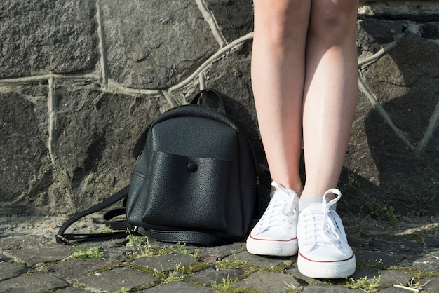 Close up teenage girl with backpack on the ground