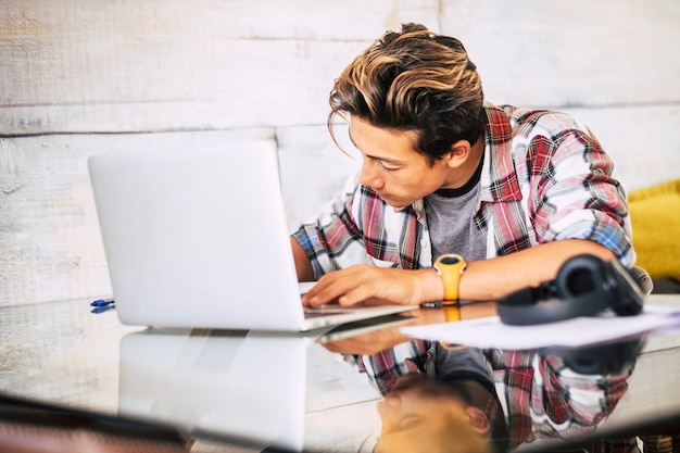 Close up of teenager with headphones staring at laptop doing his homework in silence - indoor focus guy