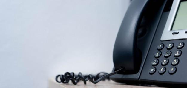 ビジネスと通信技術の概念のためのオフィスで電話voip固定電話を閉じる