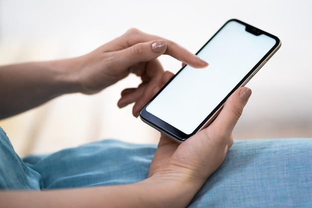 Close-up of a telephone with a white screen in female hands. a woman with a beautiful manicure holds a phone. modern technologies, smartphone. copy space.