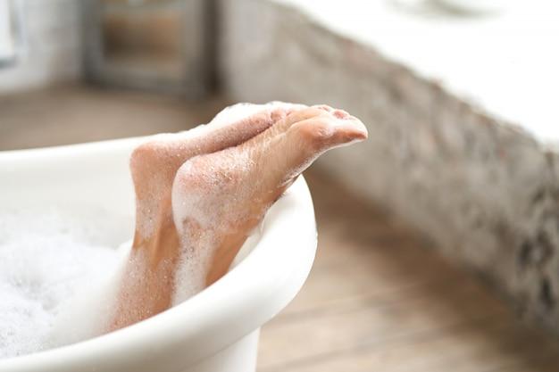 せっけんの泡が付いた白いバスタブで柔らかい女性の足をクローズアップ。明るいバスルームで水泳を楽しむ女性