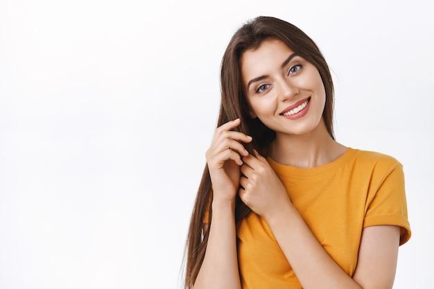 Primo piano tenero, ragazza seducente femminile che si prende cura dei suoi capelli, toccando le ciocche inclinano la testa e sorridendo, soddisfatta del buon prodotto per la cura dei capelli che ha applicato per fare l'acconciatura, sfondo bianco