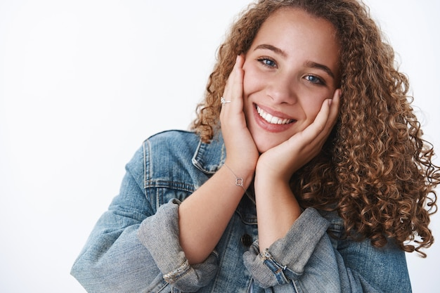 Close-up tender happy delighted excited charming curly-haired chubby girlfriend feeling upbeat touching cheeks joyfully blushing tilting head feeling uplifted joyful hear good news, white wall