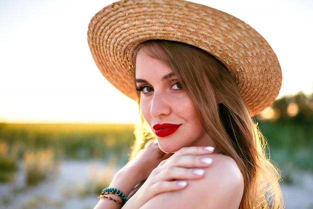 Chiuda sul tenero ritratto della donna sensuale di bellezza in posa sul campo, stile vintage, indossando il cappello alla moda di paglia, trucco di bellezza della natura, viso lentigginoso e labbra carnose rosse.