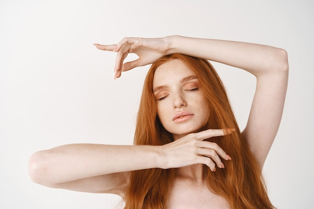 Close-up of tender redhead female model with long red natural hair, perfect skin without make-up, showing clean face, standing naked with closed eyes on white wall