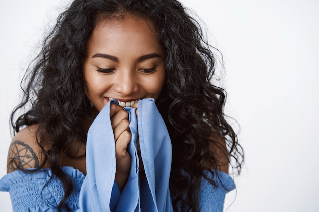 Close-up tender and romantic curly-haired female with clean skin, no blemishes, laughing happily, hold hands near smiling mouth, standing white wall enthusiastic