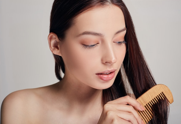 Close up a tender woman with a playful mood combs her hair with a light brown comb on the looks