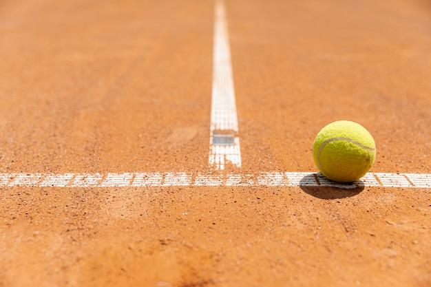 Pallina da tennis del primo piano sulla terra del campo