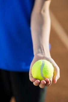 Close up tennis ball held in hand