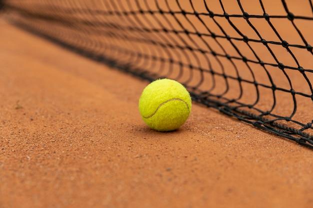 Close-up tennis ball next to net