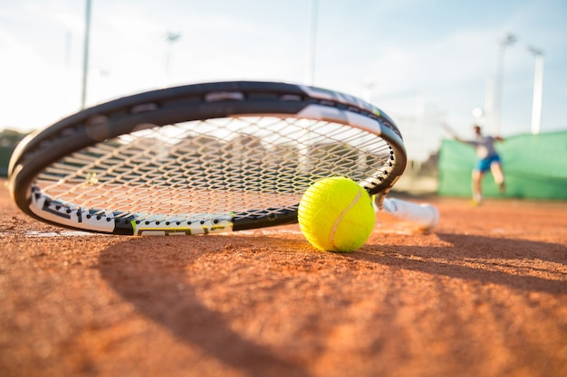Close-up tennis racket and ball placed on court ground while player hitting ball.